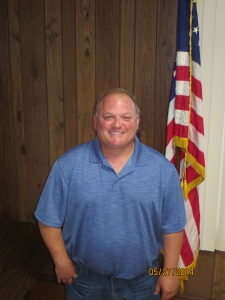 Image of Highway Commissioner Danny Picarella wearing a blue collared shirt in front of the American flag.