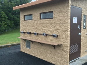 Image of the personal electronic device charging station. which has five charging plugs, located on the left side of the All Season Bathroom building located in Edwardsville Township Community Park